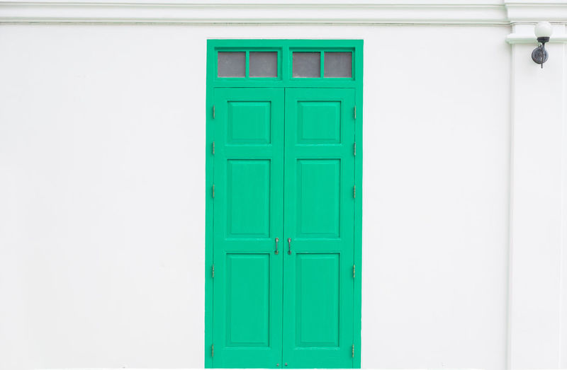 Traditional green door wooden of an old on white wall,in Thailand Architecture Building Building Exterior Built Structure Closed Day Door Door Handle Door Knob Entrance Green Color House Outdoors Protection Residential District Safety Security Traditional Turquoise Colored Wall - Building Feature White Color Wood - Material Wooden