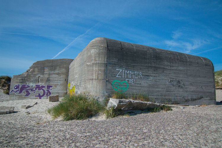 """Shot in low angle with wide lense, on Grenen Beach near Skagen. It says """"free room"""" aka """"Zimmer frei"""", as a monument and memorial of WW2. Shot 2017. Architecture Beach Beach Life Beach Photography Beachphotography Blue Sky And Clouds Built Structure Bunker Bunker Bay Concrete Wall Concretedesign Day Depth Of Field Grass Gravel History Low Angle View Monument No People Outdoors Sharpness Sky Text Wide Angle Lens World War 2 Memorial"""