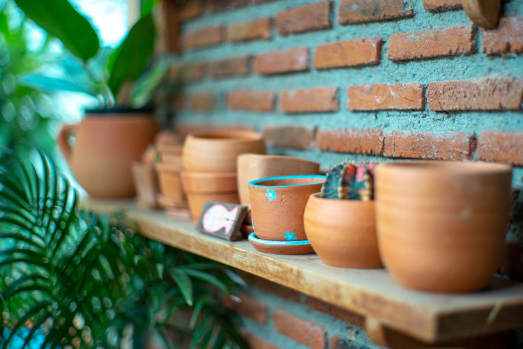 View of potteries on shelf by wall