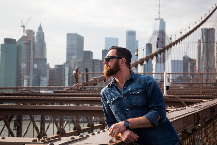 Mature man standing on brooklyn bridge in city