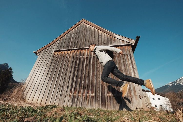 Low Angle View Of Man Levitating By Barn Against Blue Sky