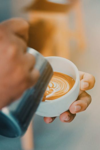 Midsection of man holding coffee cup