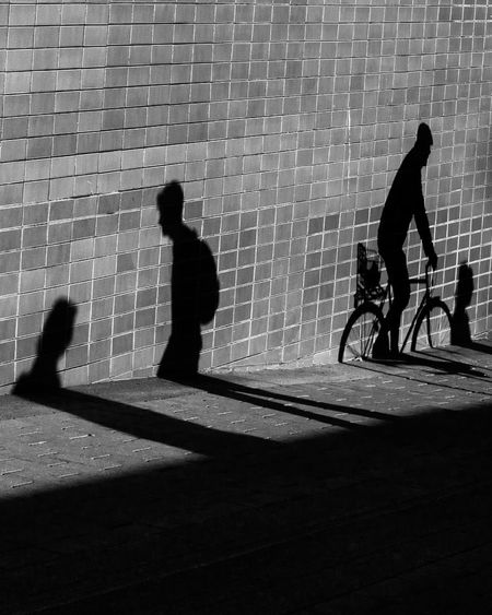 Silhouette people walking on footpath