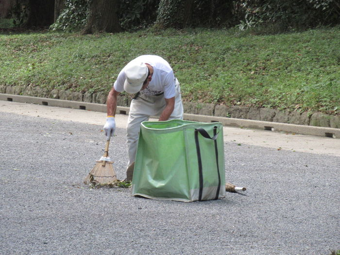 Man working on garbage bin by road