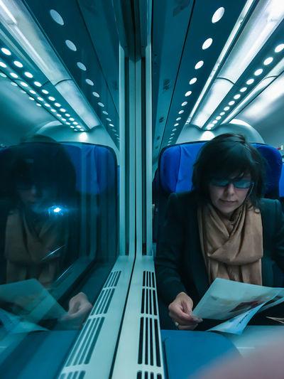 Woman Sitting In Illuminated Subway Train