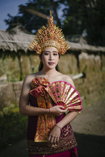 Portrait of young woman wearing traditional clothing standing on land