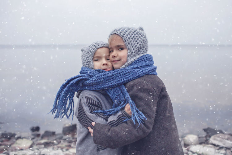 Portrait of smiling siblings embracing by lake during winter