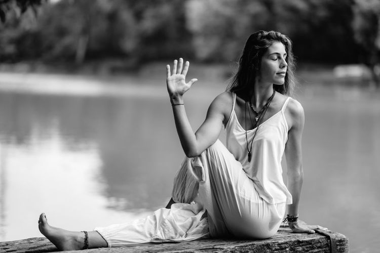 Yoga Woman by The Lake. Seated Spinal Twist Yoga Nature Meditation Water Lake Woman Meditate Lifestyle Mindfulness Young Exercise Beautiful Balance Outdoor Sitting Relax Female Concetration Tranquility Spirituality Inner Peace Black And White Seated Spinal Twist Stretching Flexibility