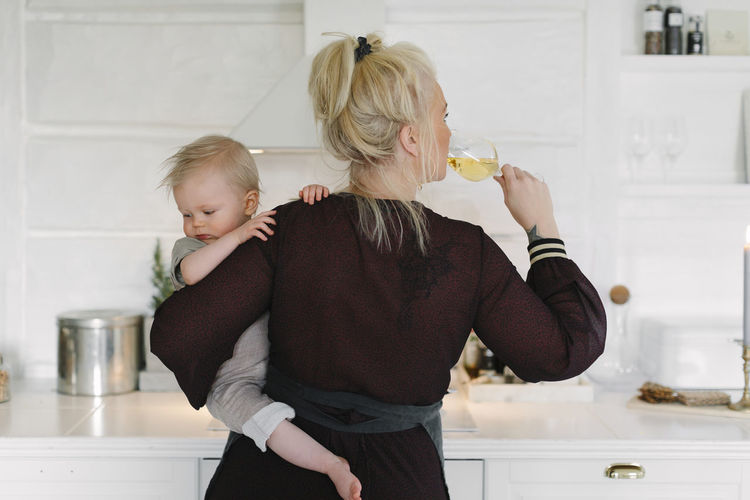 Rear view of mother and daughter at home