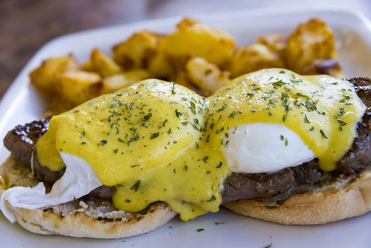 Close-up of eggs benedict with sirloin steak served in plate