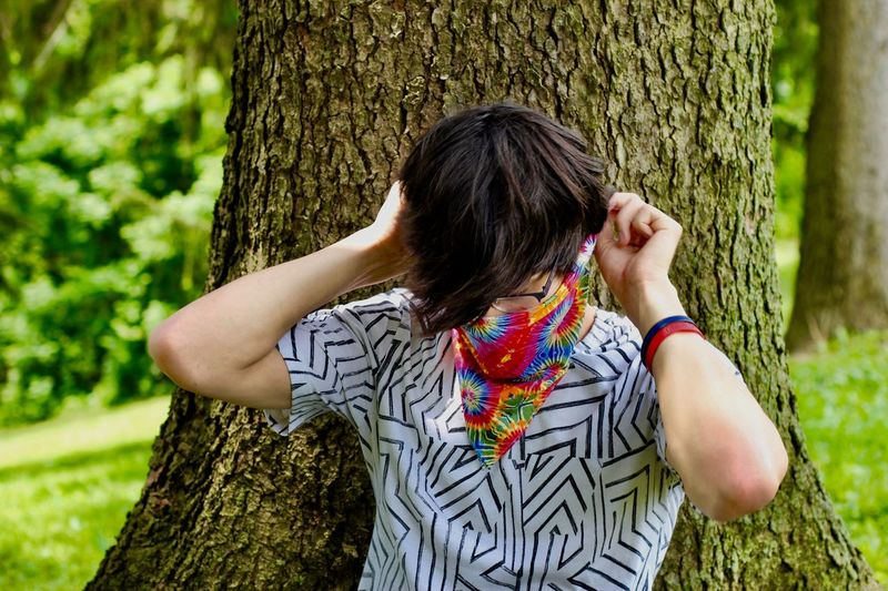 Young man tying a bandana to his face against a tree Style Glasses Bandana Fashion Colorful EyeEm Selects One Person Real People Plant Leisure Activity Women Lifestyles Nature Hair Tree Trunk Trunk Hairstyle Tree Day Casual Clothing Long Hair Grass Young Adult Waist Up Land