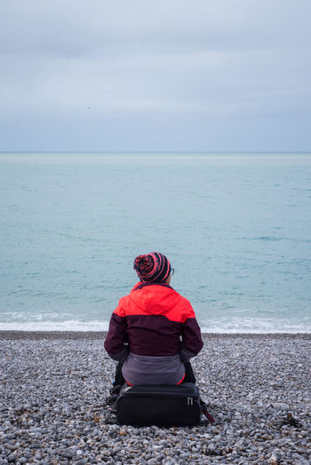 Rear view of woman sitting on beach looking at sea