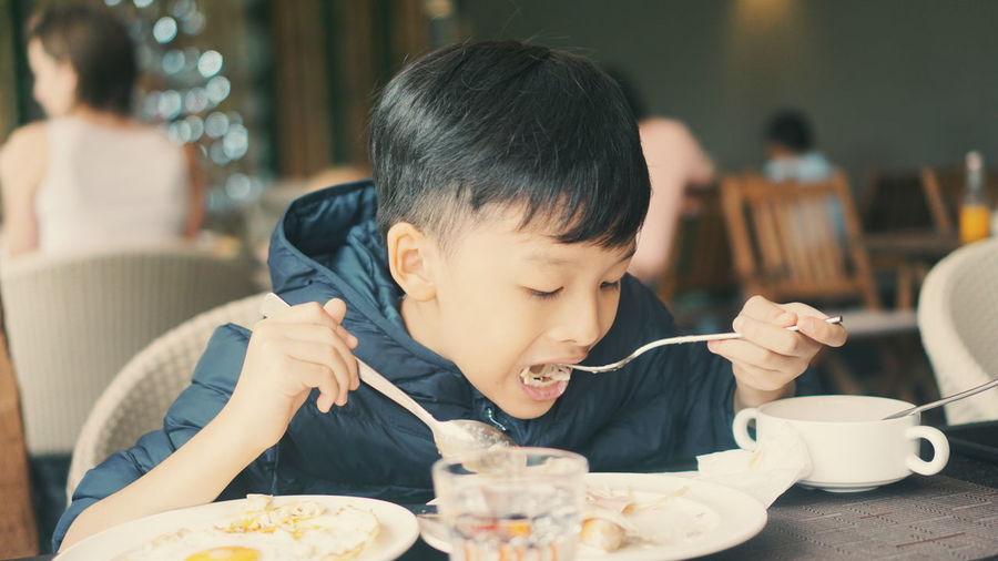 Boy eating food in restaurant
