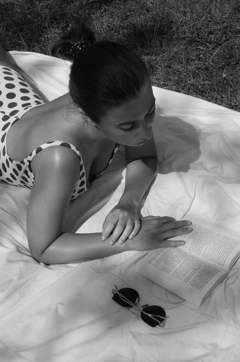 Rear view of woman lying on grass while reading book