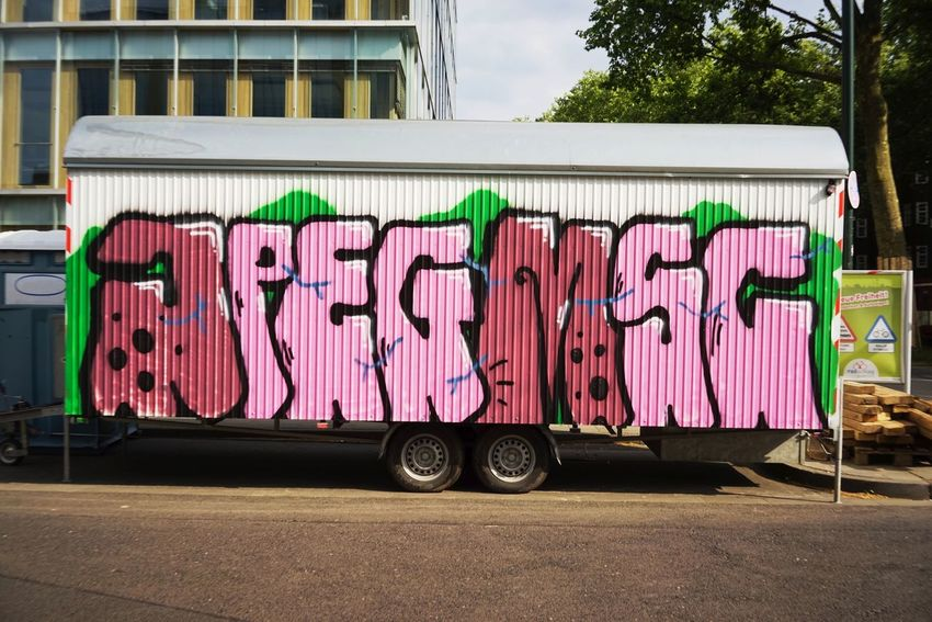 Construction Trailer Building Exterior Architecture Built Structure Day No People Text Transportation Outdoors Graffiti City Pink Color Western Script Street Multi Colored