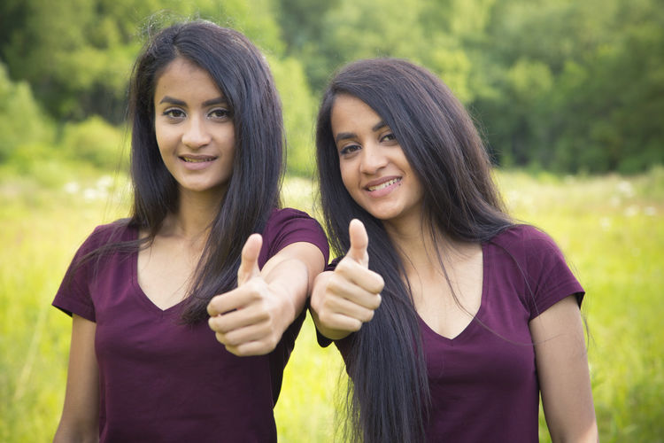 Portrait of beautiful twins showing thumbs up while standing on field
