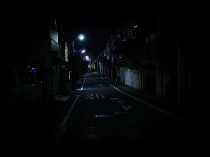 Surface level of empty road along buildings at night