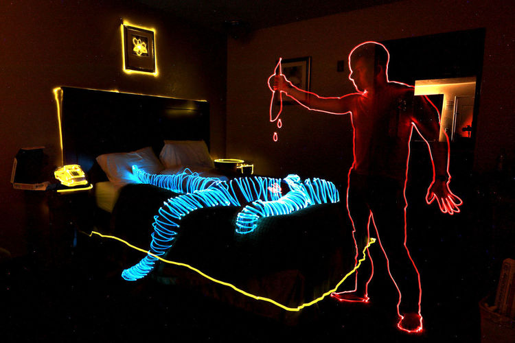 Midsection of woman with illuminated lighting equipment at home