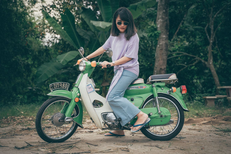 Beautiful woman riding a classic motorcycle Bicycle Transportation Casual Clothing One Person Land Vehicle Lifestyles Leisure Activity Real People Young Adult Mode Of Transportation Day Women Tree Sport Plant Nature Focus On Foreground Young Women Full Length Outdoors Riding Beautiful Woman Hairstyle Honda C70 Honda Motorcycle