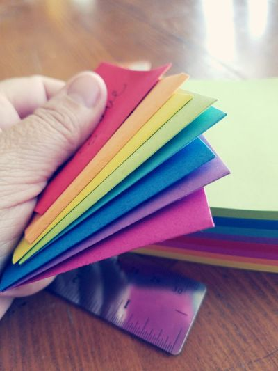 Cropped hand holding colorful adhesive notes on table
