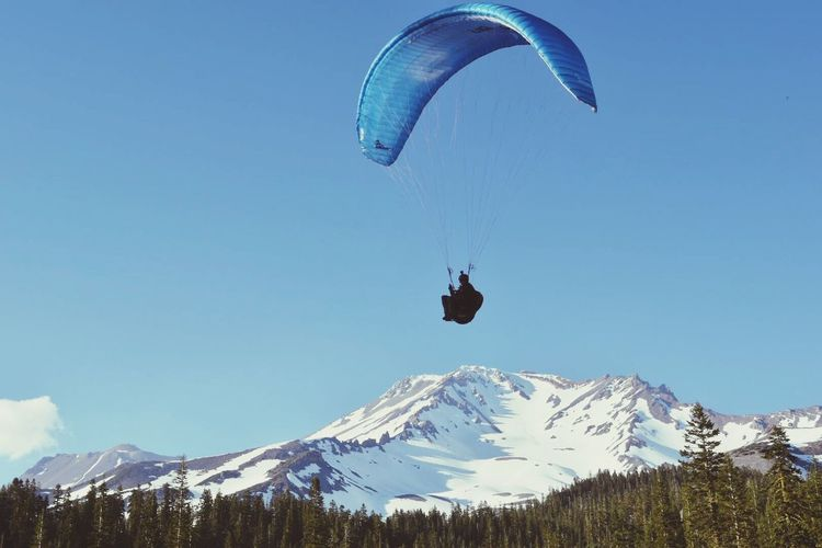 Low Angle View Of Silhouette Person Paragliding Over Landscape Against Blue Sky
