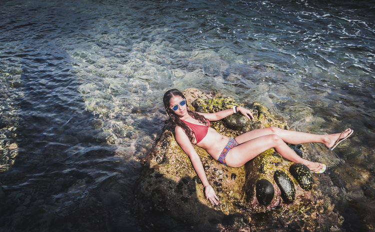 Mermaid that rocks! Beautiful Woman Beauty In Nature Bikini Day Full Length High Angle View Leisure Activity Lifestyles Lying On Back One Person Outdoors Real People Sea Vacations Water Young Women The Portraitist - 2017 EyeEm Awards