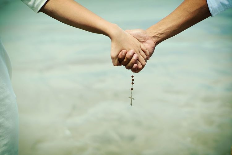 Cropped image of couple holding hands
