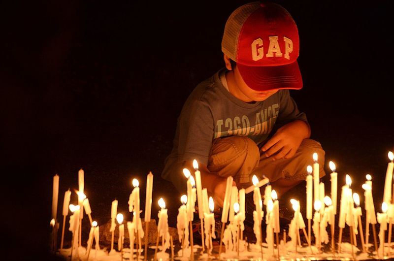 Midsection of man holding illuminated candles