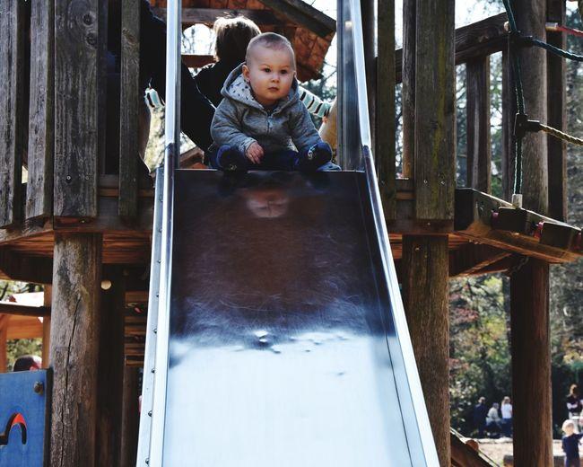 Cute boy sitting on slide in playground