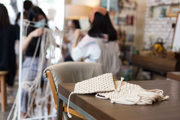 macrame workshop in cafe. Adult Bag Business Casual Clothing Chair Clothing Craft Detail Focus On Foreground Hair Hairstyle Incidental People Indoors  Lifestyles Long Hair Macrame One Person Pattern Real People Relaxation Seat Sitting Table White Women