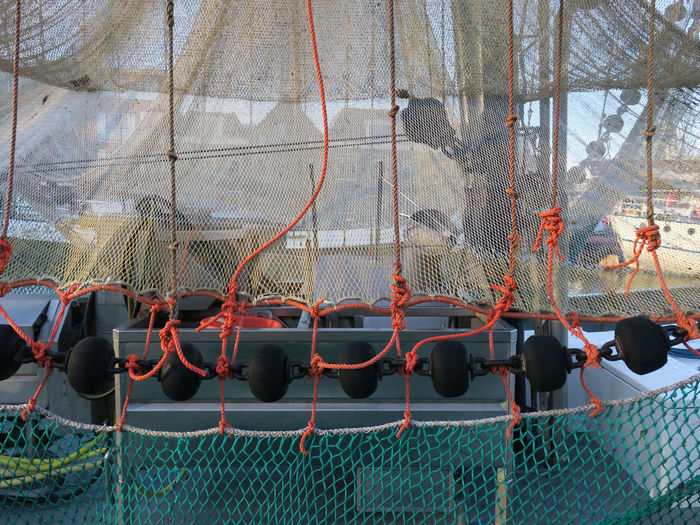 fishing nets hanging out on a trawler Harbor Fishing Boat Fishing Nets Ropes Orange Color Fishing Nets In The Port Water Fishing Industry Fish