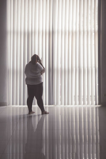 Rear view of overweight woman standing against window at home