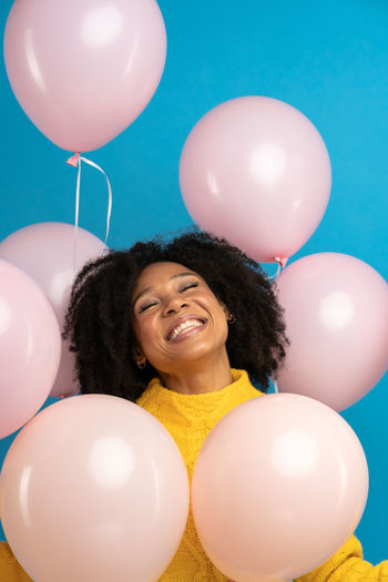 Portrait of a smiling young woman with balloons