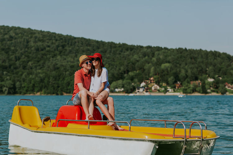 Shot of happy couple sitting on pedal boat. Young man and woman in love enjoying boating in the lake. Boating Couple Date Holiday Horizontal Love Man Romantic Summertime Vacations Woman Young Boat Boyfriend Caucasian Day Girlfriend Lake Outdoors Pedalo Relax Sea Summer Two People Water
