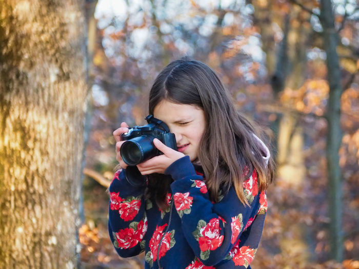 Girl photographing with camera in forest