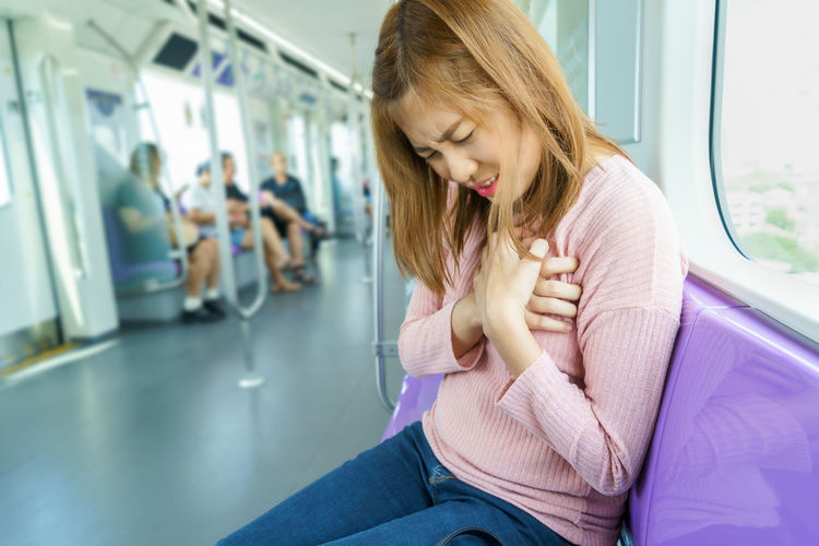Woman with chest pain sitting in train