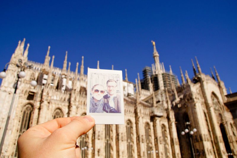 Cropped Hand Of Man Holding Photograph Against Milan Cathedral
