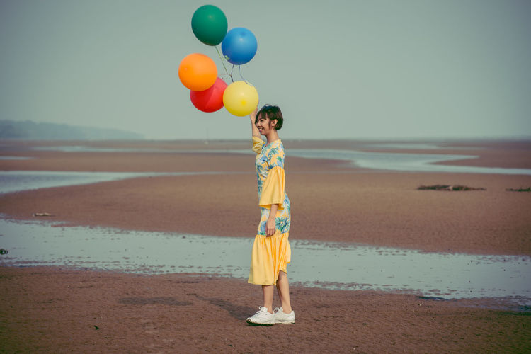 Side view full length of young woman holding colorful balloons at beach