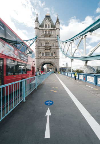 Road sign on bridge against sky in city