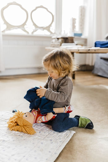Toddler girl dressing doll in living room - Hindeloopen, Friesland, Netherlands Girl Toddler  Toddlerlife Germany Caucasian Getting Dressed Dressing Up Jeans Stuffed Toy Playing Learning Doll Toy Sitting On Floor Clothing Education Window Living Room Table Serious Looking Down Holding Concentration Challenge Happiness Childhood Child Full Length One Person Indoors  Sitting Real People Home Interior Lifestyles Casual Clothing Innocence Leisure Activity Flooring Girls Focus On Foreground Females Hair Hairstyle
