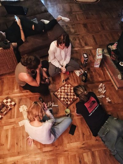 High Angle View Indoors  Togetherness Directly Above Men Hardwood Floor Table Sitting Adult Women Group Of People Lifestyles People Eating Real People Food Friendship Adults Only Day Young Adult Winter