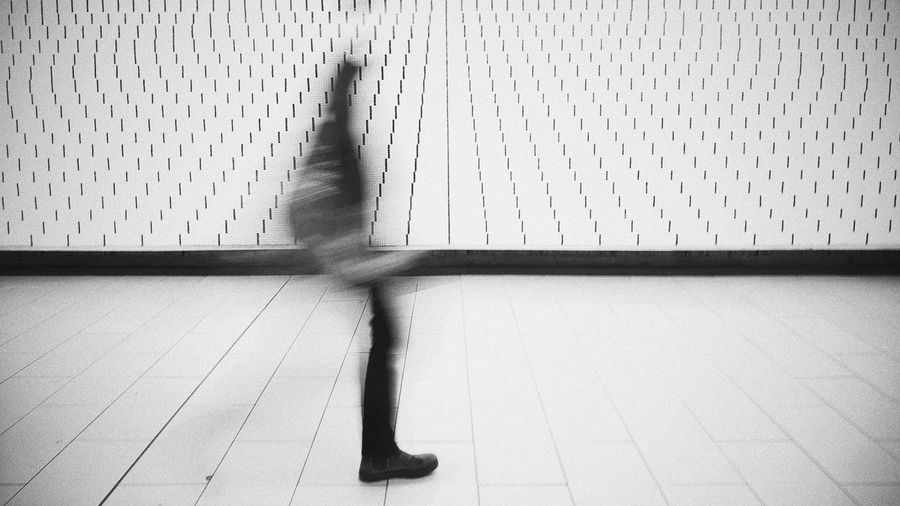 Blurred motion of woman walking on tiled floor