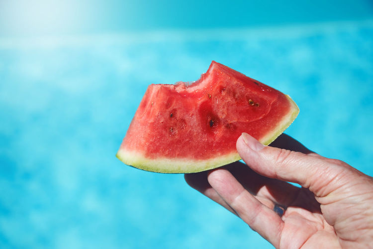 Cropped hand holding melon slice against swimming pool
