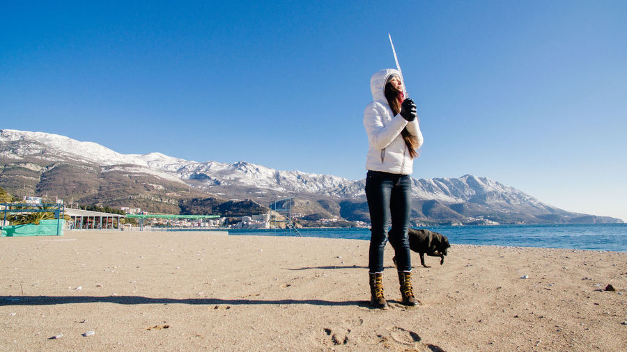 Woman holding icicle while standing with dog at beach against sky
