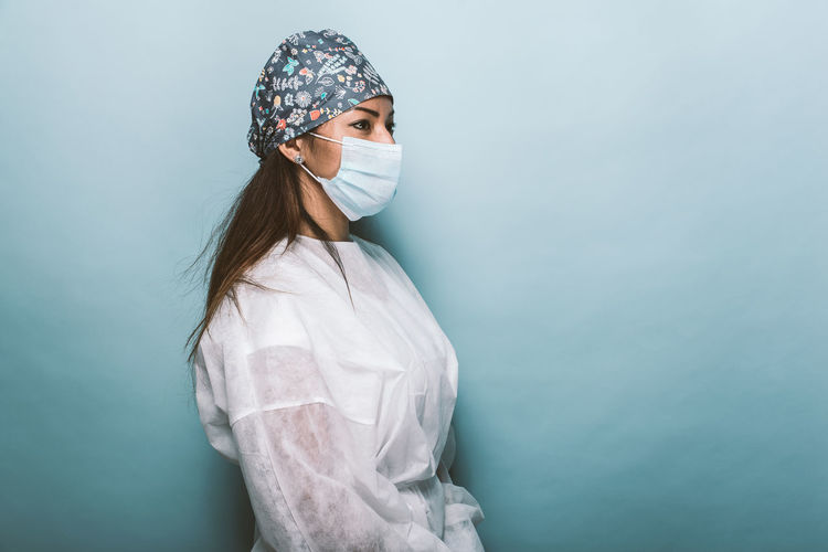 Side view of doctor wearing mask standing against wall