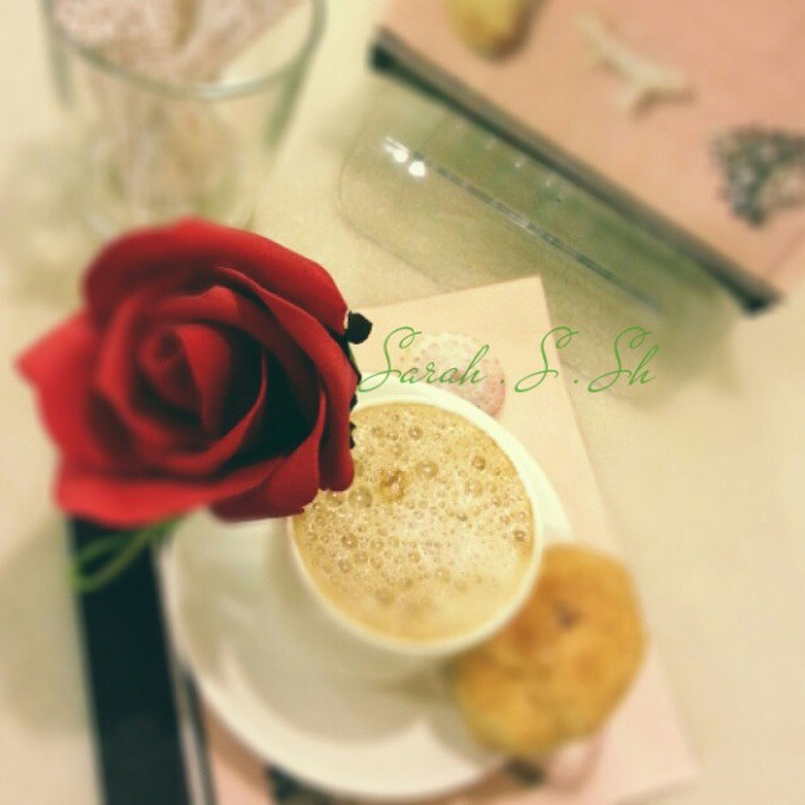 indoors, food and drink, freshness, table, still life, text, close-up, western script, communication, coffee cup, drink, food, flower, selective focus, sweet food, refreshment, focus on foreground, high angle view, coffee - drink, red
