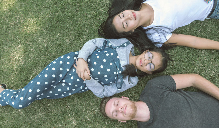 Directly Above Shot Of Friends Napping On Field At Public Park