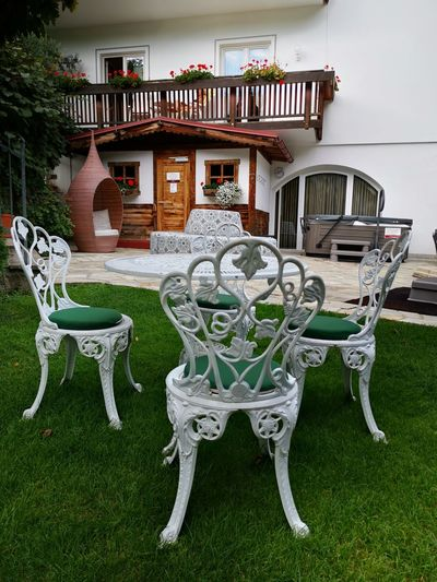 Chairs and table in lawn outside building