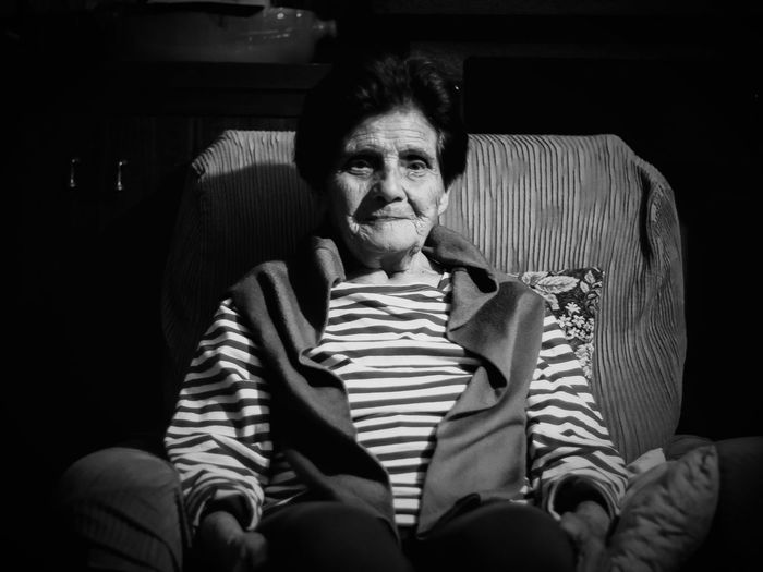 Portrait Of Senior Woman Relaxing On Armchair In Darkroom At Home