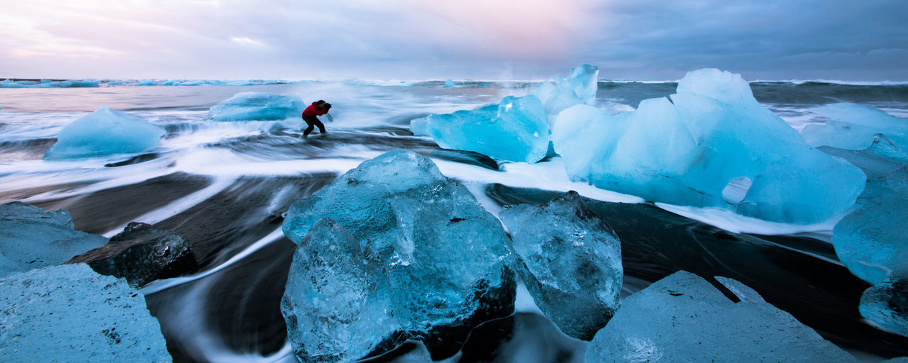 Panoramic view of woman standing at beach by icebergs during winter